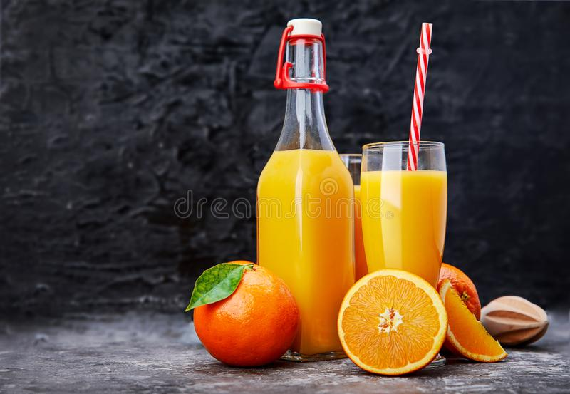 Freshly squeezed orange juice in glass bottle. With straw. Fruity still life on black backdrop and grey concrete surface rustic style stock photography