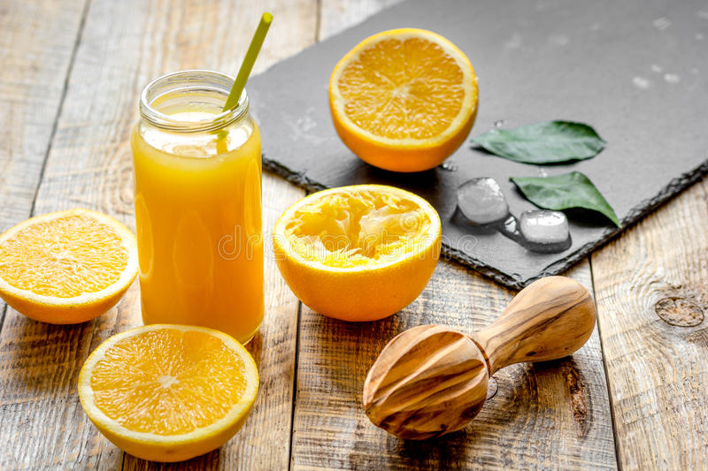 Freshly squeezed orange juice in glass bottle on wooden background. Close up royalty free stock photography