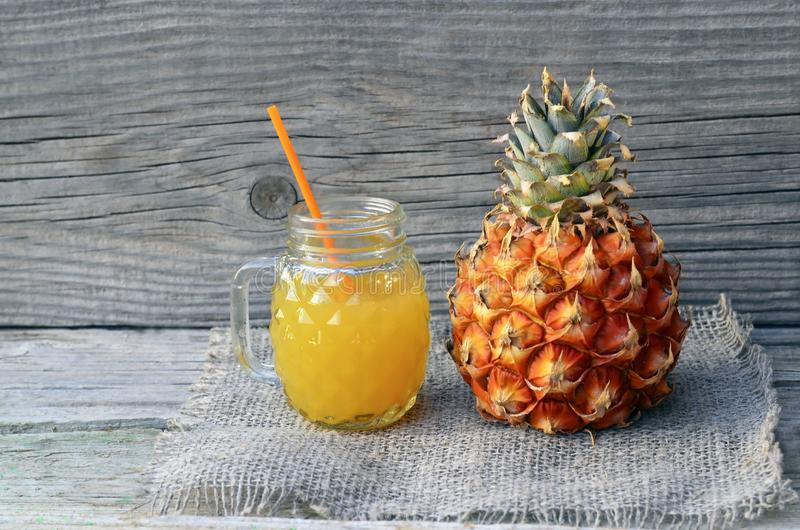 Freshly squeezed pineapple juice in a glass cup with drinking straw and ripe ananas fruit on old wooden table. royalty free stock photography