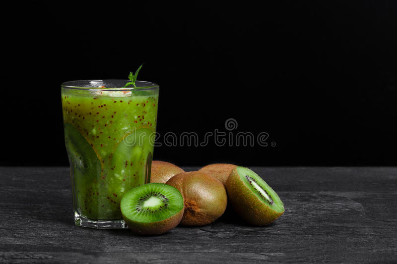 A freshly squeezed sweet cocktail from kiwi with mint on a stones desk and on a black background. Organic fruits. royalty free stock photos