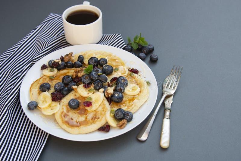 Freshmade, eigengemaakte pannekoeken met bosbes, droge vruchten en honing Ontbijt met koffie en pannekoeken Deliciious gezond voe stock foto