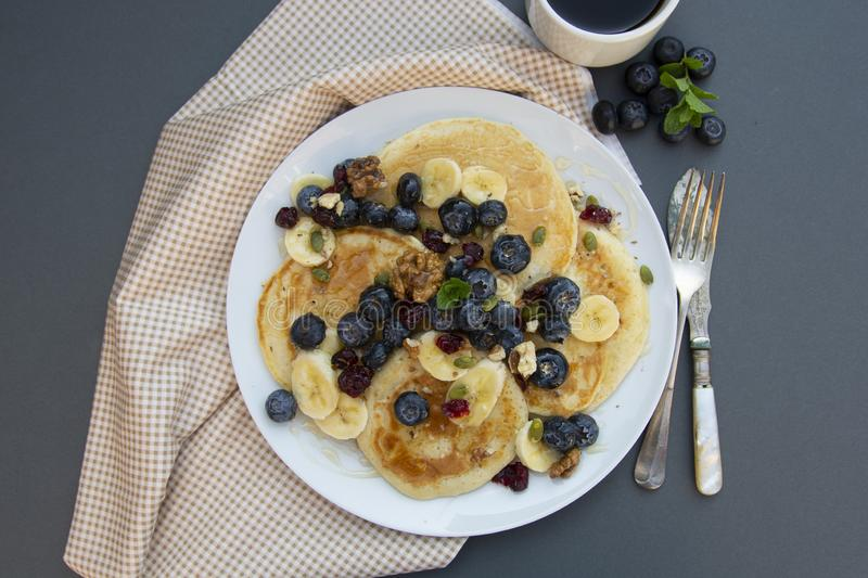 Freshmade, homemade pancakes with blueberry, dried fruits and honey. Breakfast with coffee and pancakes. Deliciious healthy food royalty free stock images