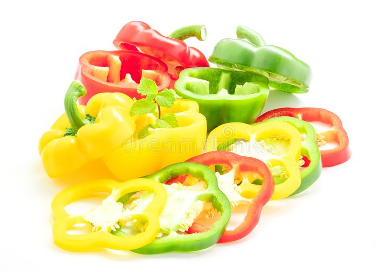 Freshness of thinly sliced sweet peppers. Overlaid with mint,  on white background royalty free stock image