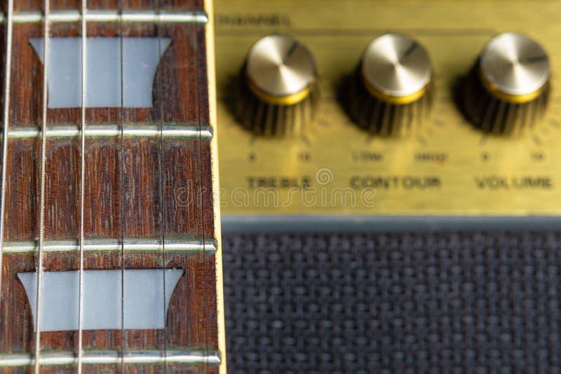 Fretboard de guitare et détail de marqueur de frette, vieux boutons brouillés d'amplificateur à l'arrière-plan photo libre de droits