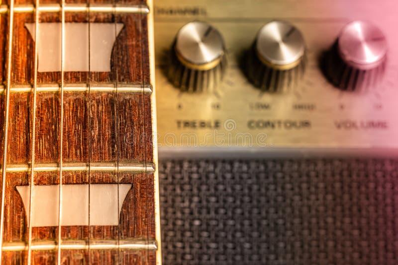 Fretboard de guitare et détail de marqueur de frette, vieux boutons brouillés d'amplificateur à l'arrière-plan image libre de droits