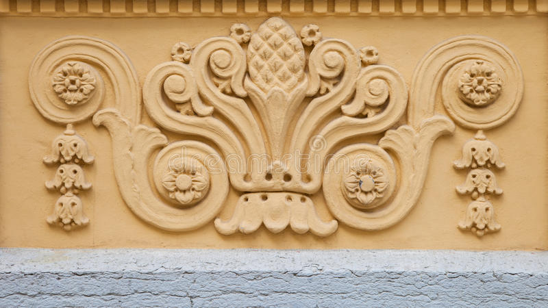 Fretwork on the building wall. Fretwork on yellow building wall stock photo