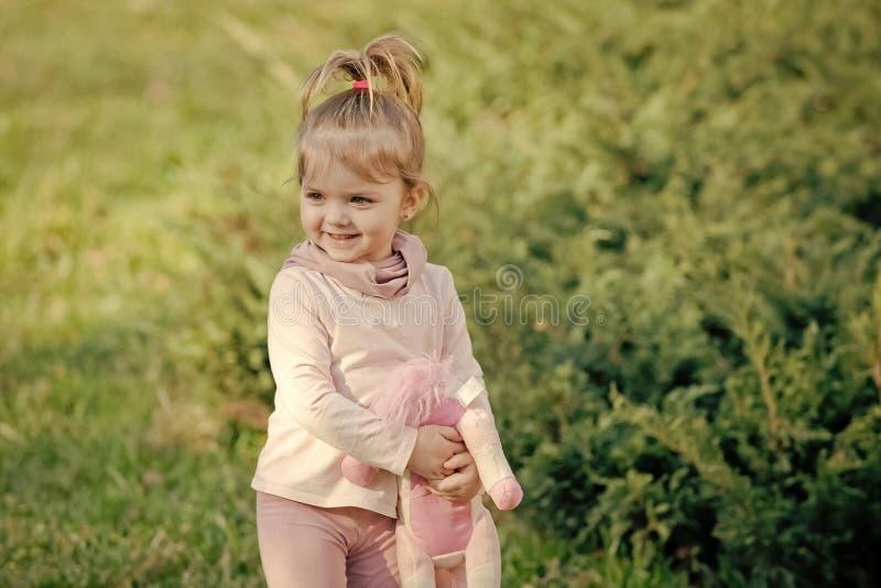 Freude am Kind Glückliches Mädchen mit weichem Spielzeuglächeln auf natürlichem Hintergrund stockfoto
