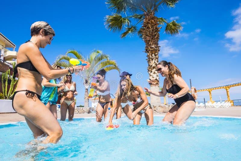 Freude und Freundschaft mit einer Gruppe von Frauen, die sich im Schwimmbad mit Wasserpistolen amüsieren - Sommerurlaub lizenzfreie stockfotos