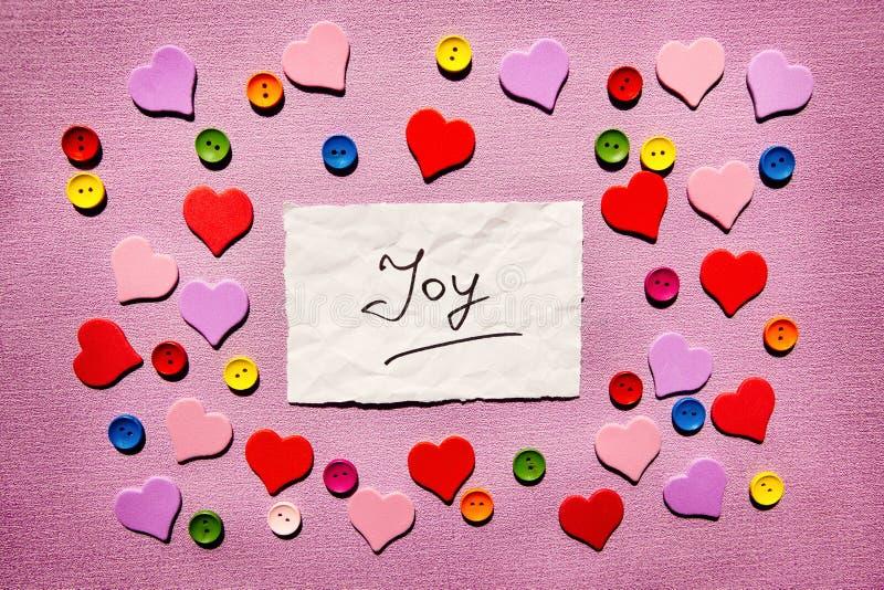 Freude - Wort auf rosa Hintergrund mit bunten Herzdekorationen lizenzfreie stockbilder