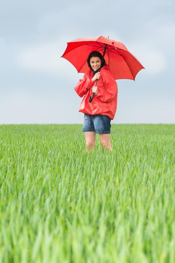 Freudig erregt Jugendliche, die roten Regenschirm hält stockfotografie