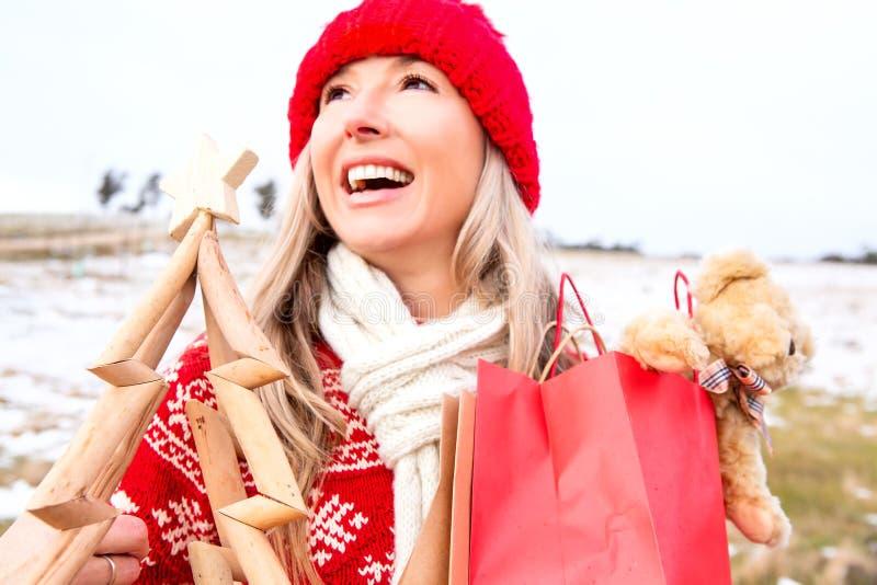 Freudige Frau, die kleine hölzerne Weihnachtsbaum- und Geschenktaschen hält stockfotos