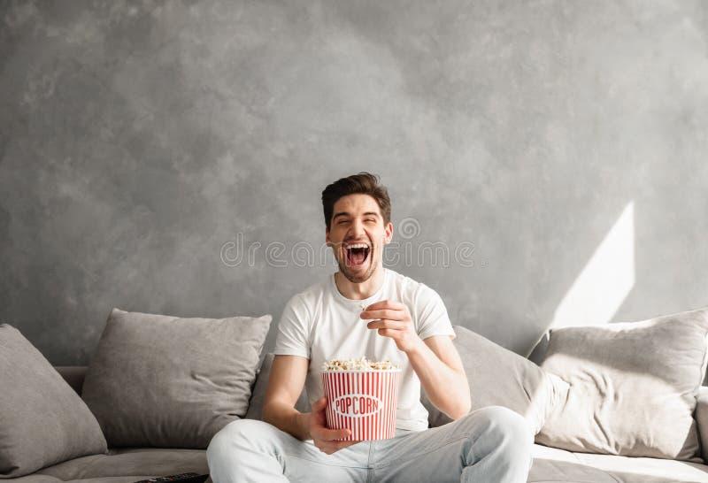 Freudiger junger auf Sofa im Wohnzimmer sitzender und lachender Mann, wh stockbilder