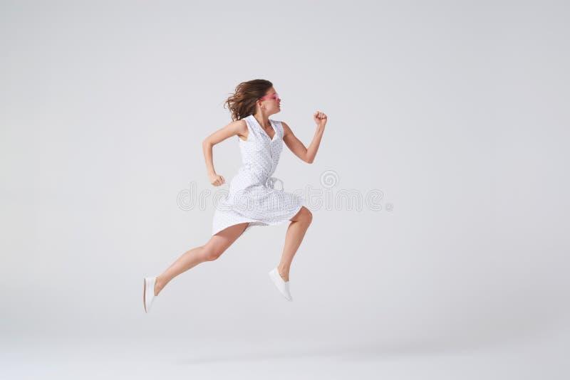 Freudiges Mädchen im Kleid, das oben in einer Luft über Hintergrund im Studio springt stockfotografie