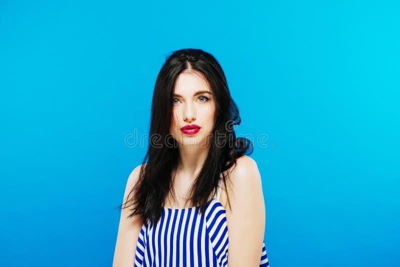 Freudiges Modell im gestreiften Sommer-Kleid, das im Studio auf blauem Hintergrund aufwirft stockfoto