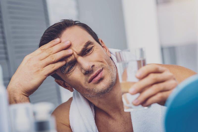 Freudloser deprimierter Mann, der das Glas des Wassers betrachtet stockbilder