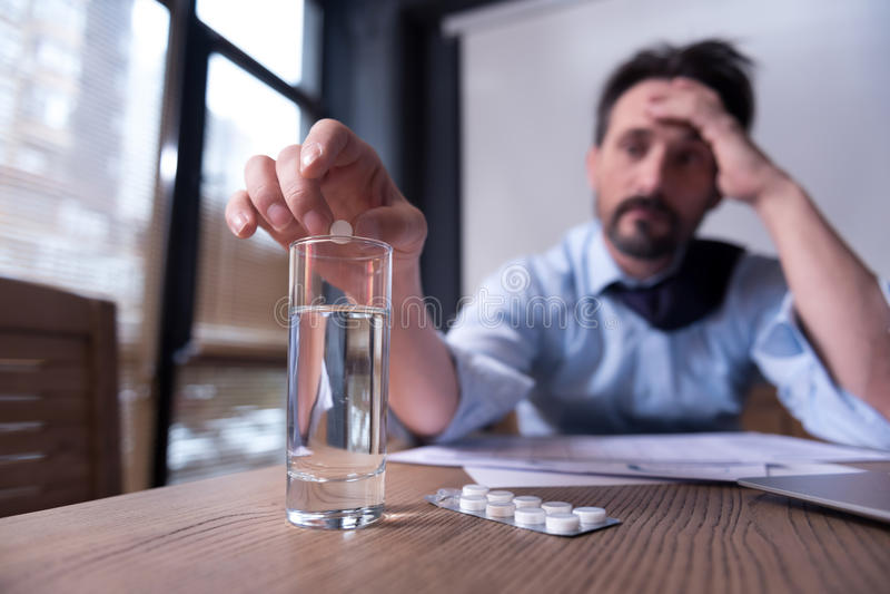 Freudloser deprimierter Mann, der Medizin einnimmt lizenzfreie stockfotografie