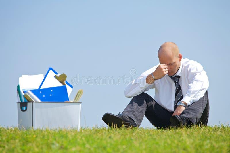Freudloser Geschäftsmann, der voll nahe bei Korb von Dateien im Park sitzt stockfotografie