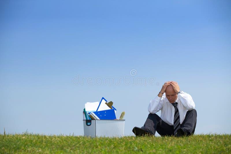 Freudloser Geschäftsmann, der voll nahe bei Korb von Dateien im Park sitzt lizenzfreies stockbild