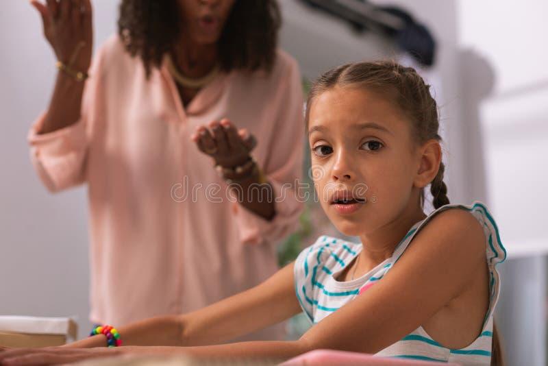 Freudloses nettes kleines Mädchen, das Sie betrachtet stockfotos