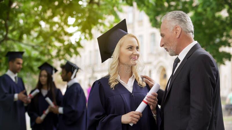 Freuendes Diplom des glücklichen blonden Studenten im Aufbaustudium mit Vater, Graduierungsfeier lizenzfreie stockfotografie