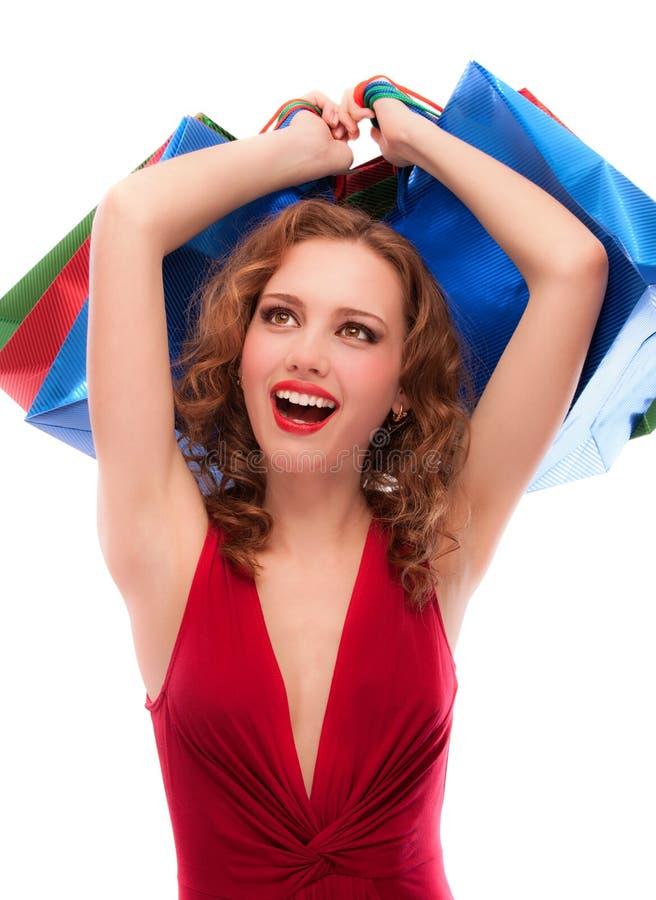 Freuendes Mädchen im roten Kleid mit Käufen lizenzfreies stockfoto