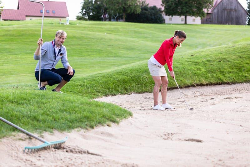Freund, der den weiblichen Golfspieler schlägt Golfball auf Bunker betrachtet stockfotos