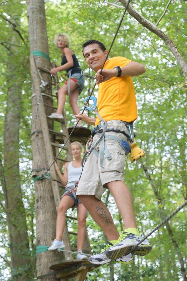 Freunde auf dem Seil, das im Erlebnispark klettert stockfoto