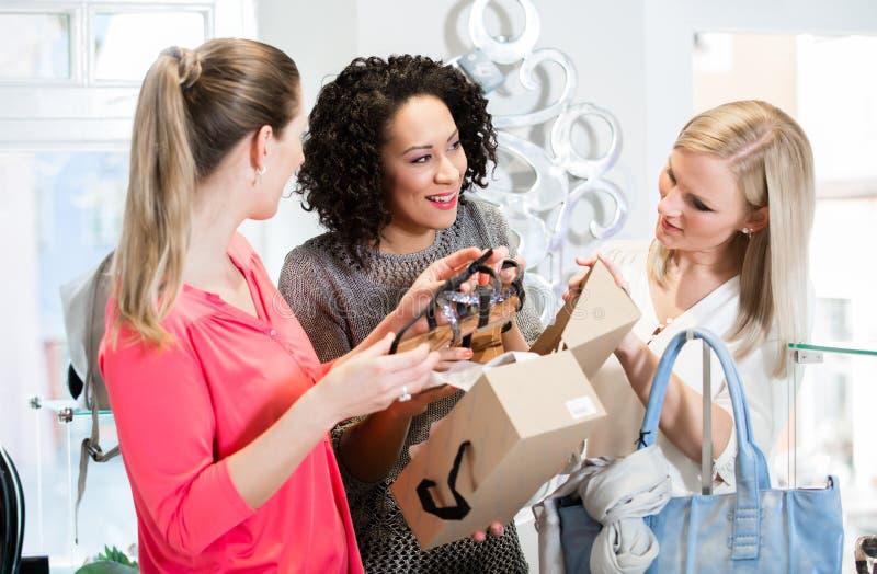 Freunde auf einem Einkaufstour Sandalen und Schuhe besprechend lizenzfreies stockbild