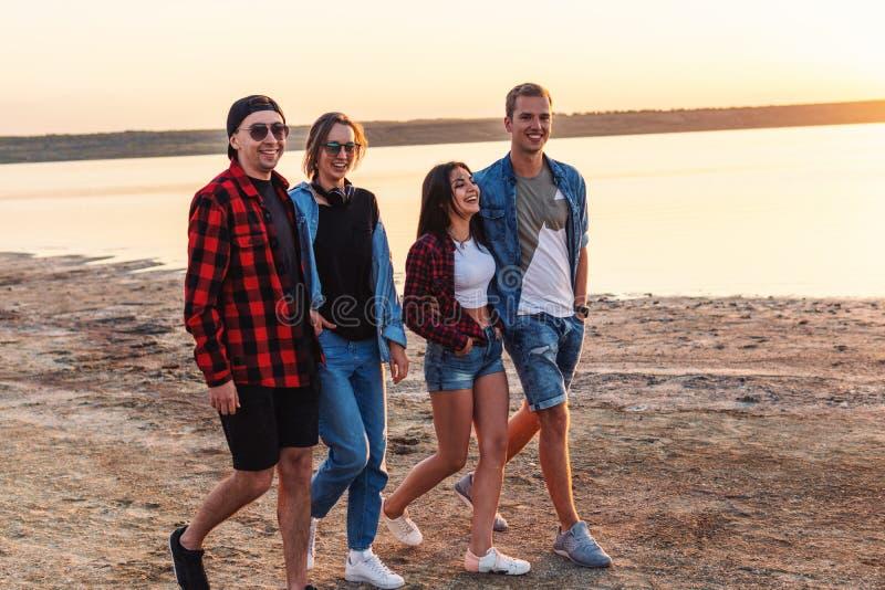 Freunde auf Strand zusammen gehend während des Sonnenuntergangs stockbilder