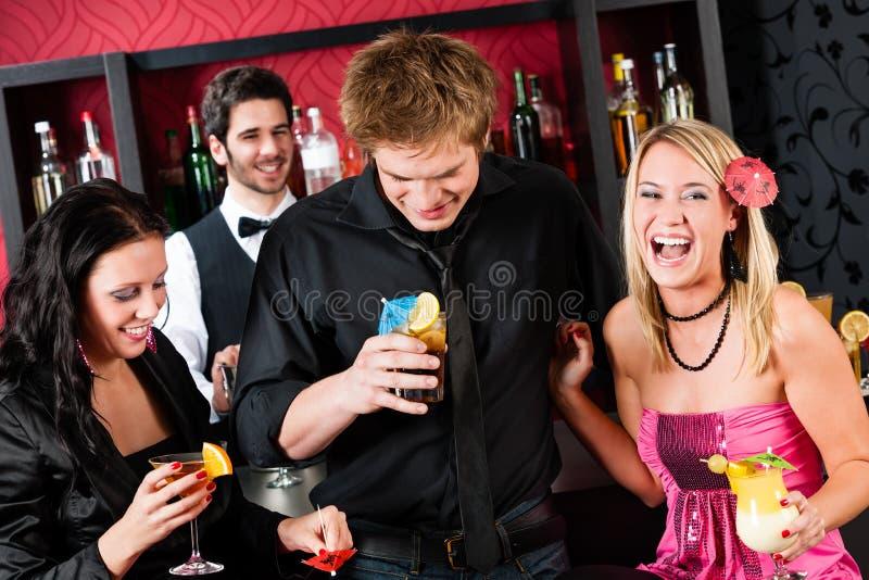 Freunde am Cocktailstab haben Partyzeit stockfoto