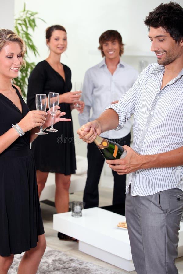 Freunde, den Champagner knallend stockbilder
