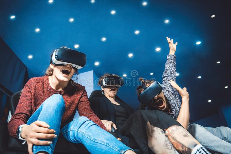 Freunde in den virtuellen Gläsern Filme im Kino mit SP aufpassend lizenzfreie stockbilder