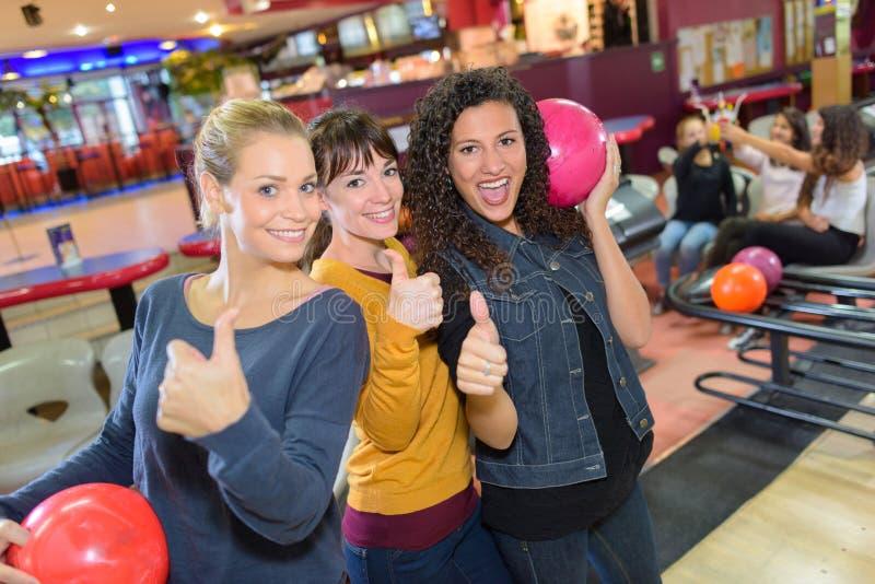 Freunde in der Bowlingspielmitte lizenzfreie stockfotografie
