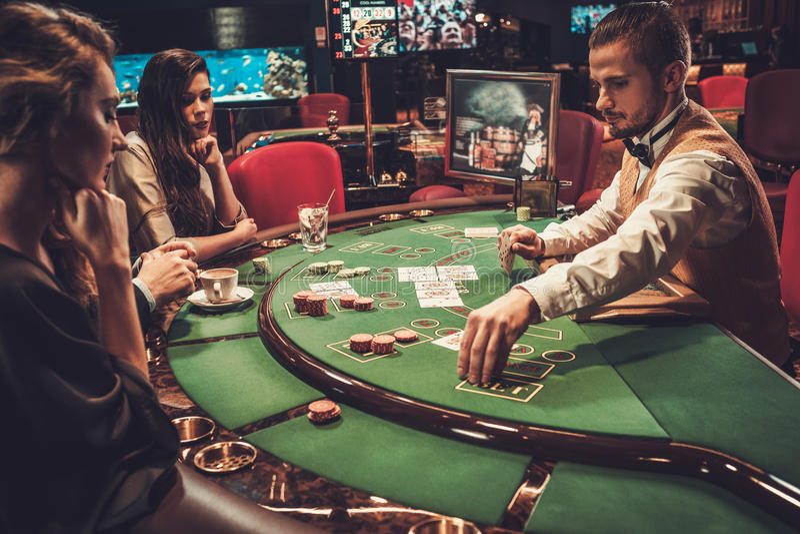 Freunde der oberen Klasse, die in einem Kasino spielen stockbilder