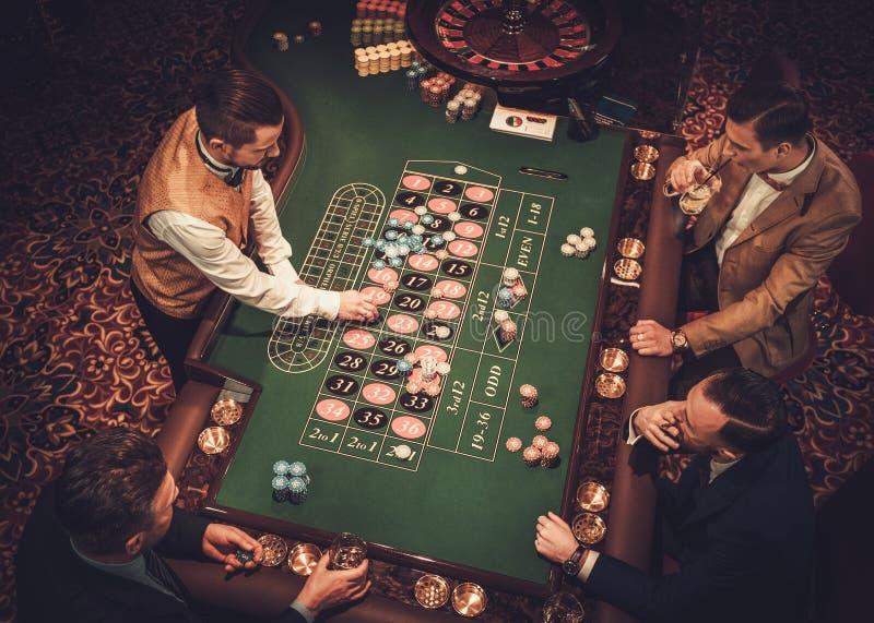 Freunde der oberen Klasse, die in einem Kasino spielen lizenzfreies stockbild