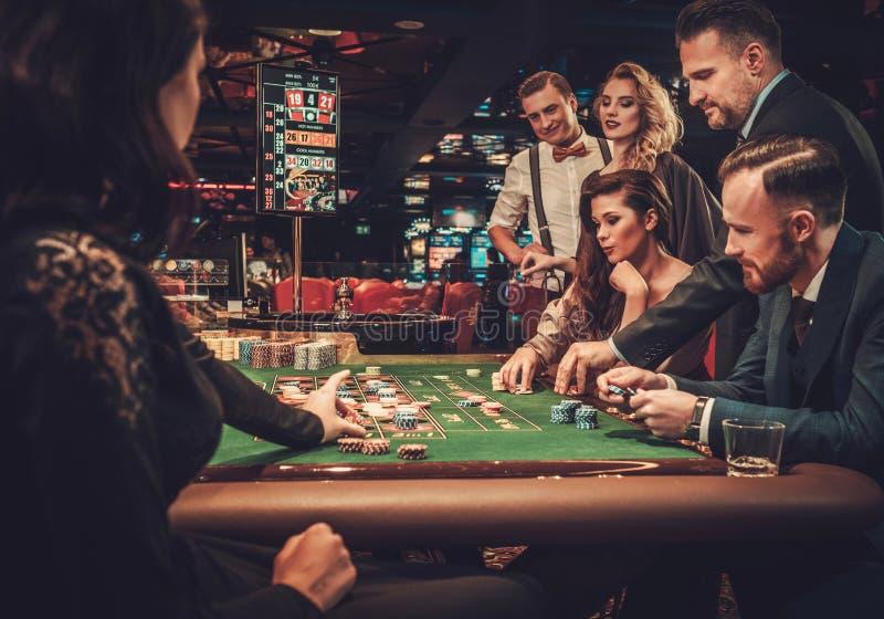 Freunde der oberen Klasse, die in einem Kasino spielen lizenzfreie stockfotografie