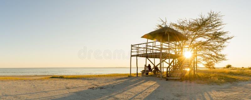 Freunde an der Sonnenuntergang-Strand-Hütte stockfotos