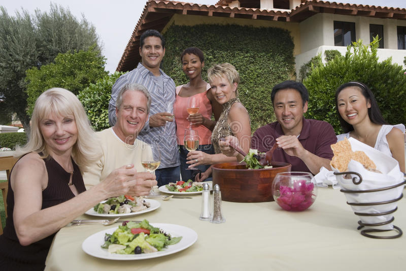 Freunde, die Abendessen im Garten genießen stockfotografie