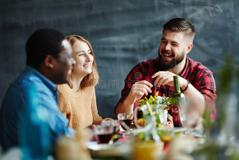 Freunde, die am Abendessen sprechen lizenzfreie stockbilder
