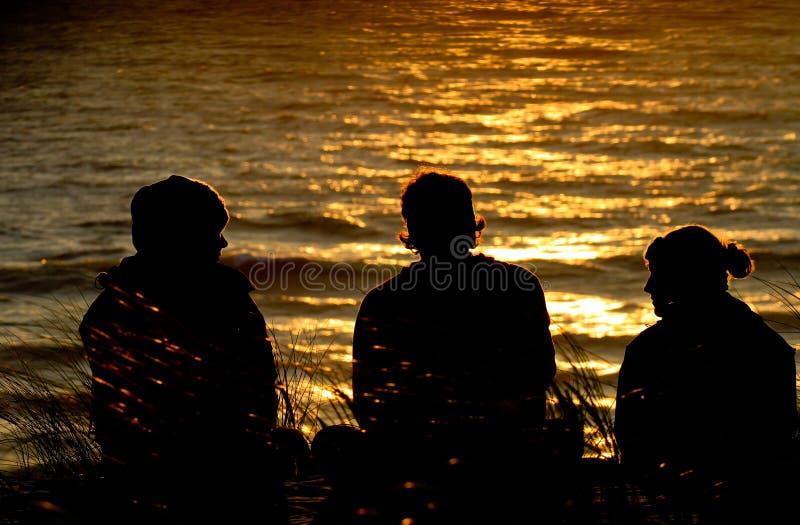 Freunde, die auf Düne im Sonnenuntergang sitzen stockfotos