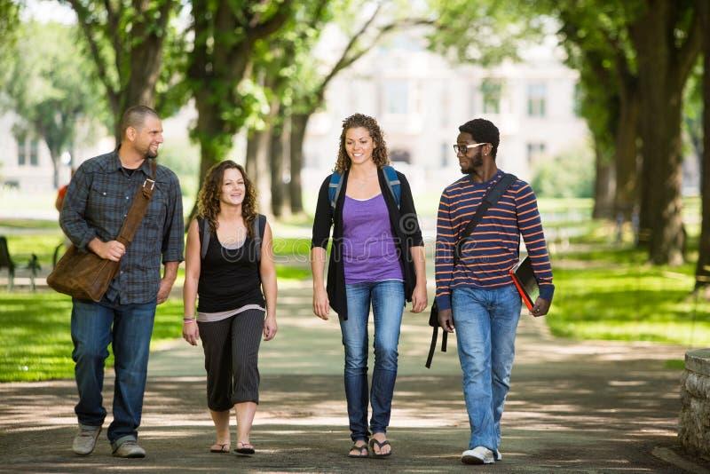 Freunde, die auf dem Campus Straße gehen stockfotos
