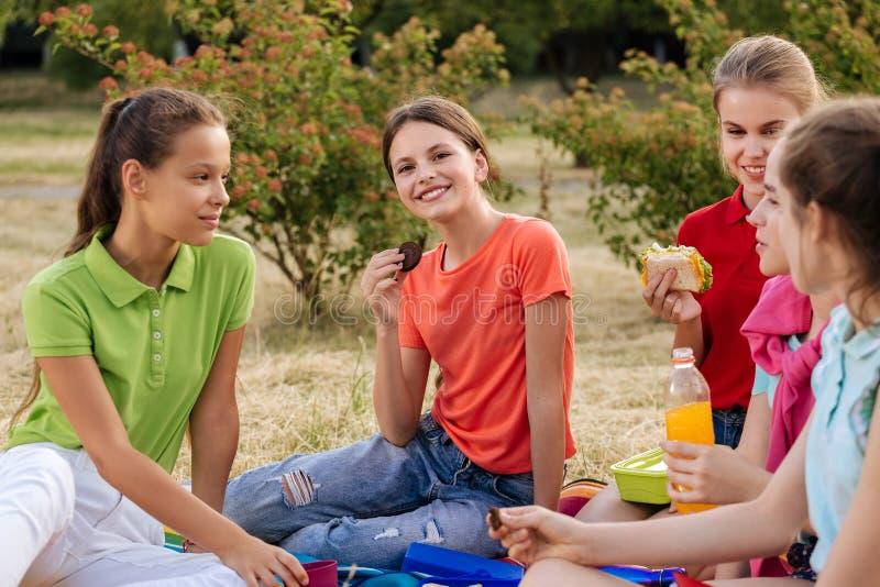 Freunde, die auf dem Gras isst gesunde Nahrung an einem Mittagessen sitzen lizenzfreies stockfoto