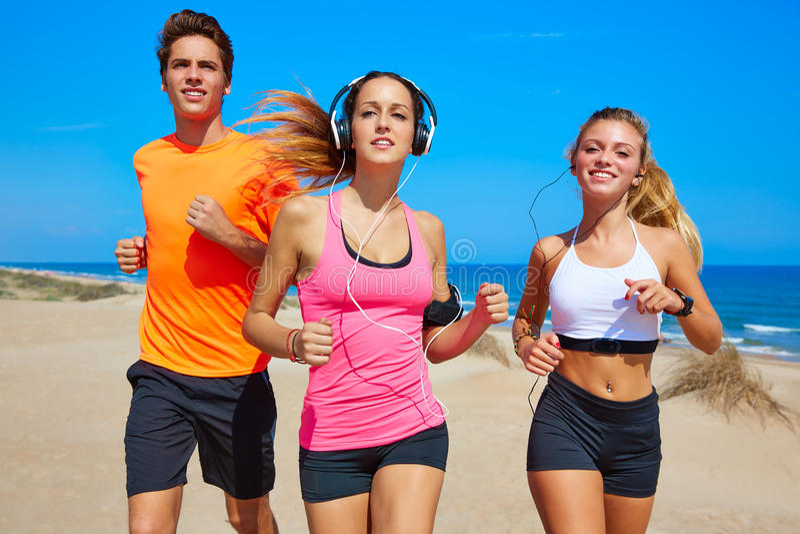 Freunde, die auf dem Strand glücklich im Sommer laufen lizenzfreie stockbilder