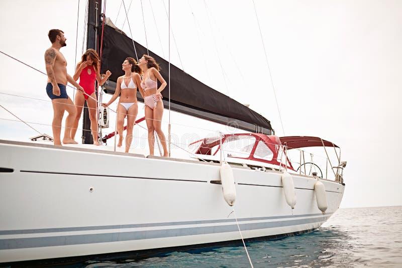 Freunde, die auf eine Yacht reisen und am Sommertag genießen Ferien, Feiertag, Sommerzeitkonzept lizenzfreie stockfotografie