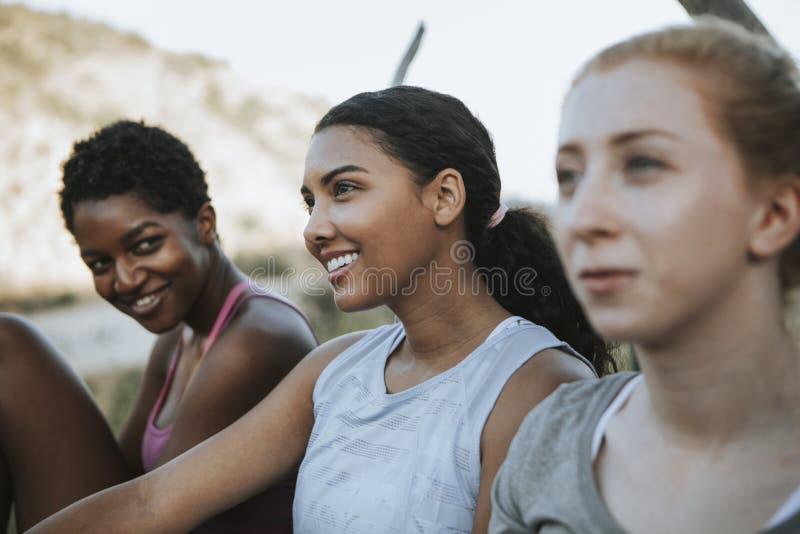 Freunde, die auf einer Parkbank sich entspannen stockfotografie