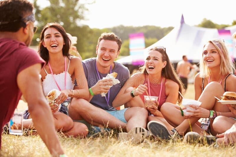 Freunde, die auf Gras sitzen und am Musikfestival essen lizenzfreie stockfotos