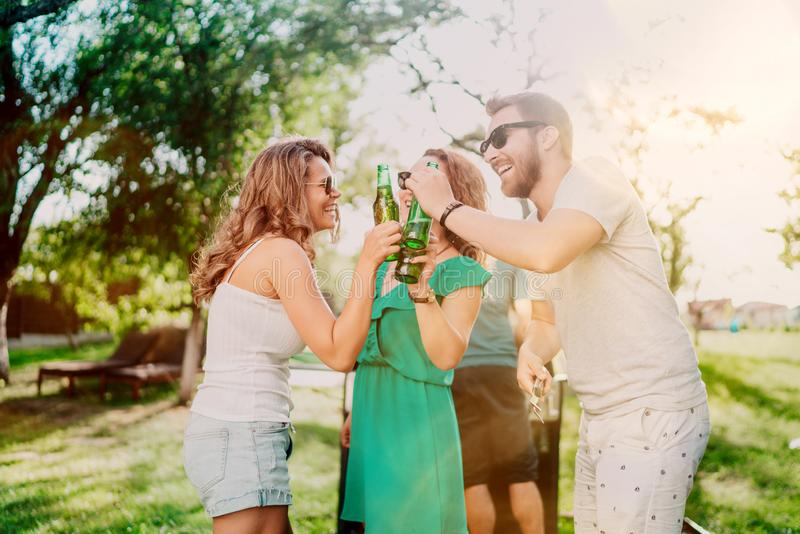 Freunde, die auf Grill während der Sommerzeit kochen Porträt von den Freunden, die eine Gartengrillpartei grillen und haben Lache stockbilder