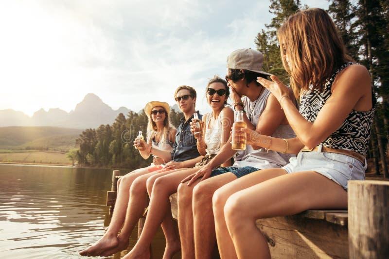 Freunde, die auf Pier an trinkenden Bieren des Sees sitzen stockfoto
