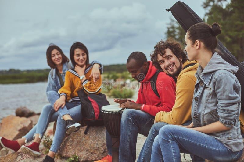 Freunde, die auf Strand sitzen und Musik hören stockfoto