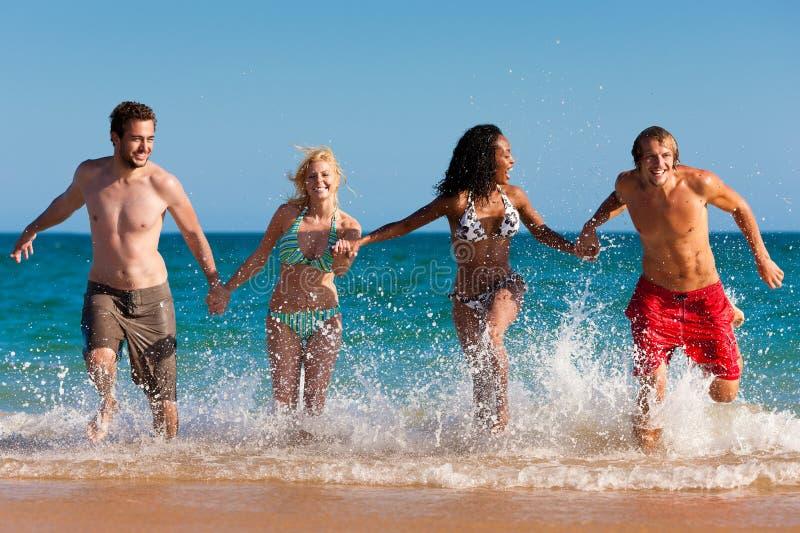 Freunde, die auf Strandferien laufen lizenzfreies stockfoto